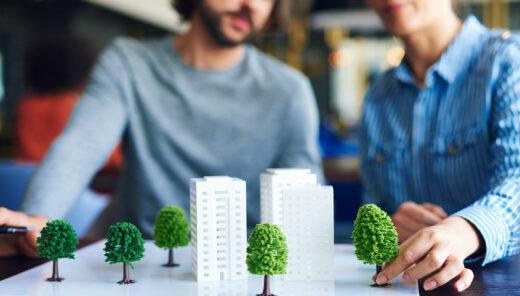 Två personer står vid ett bord med mindre modeller av byggnader och träd.