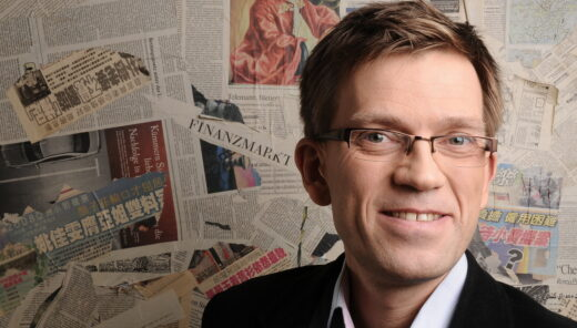 porträttbild på man med i glasögon med en backdrop av tidningar