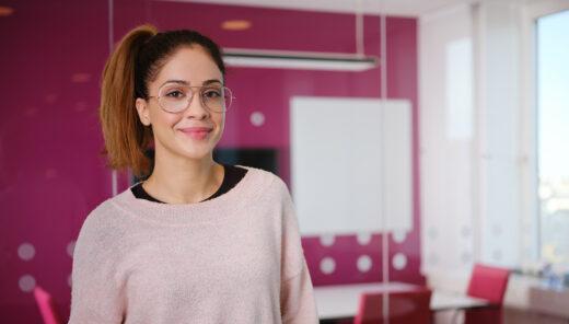 Leende kvinna i rosa tröja och glasögon
