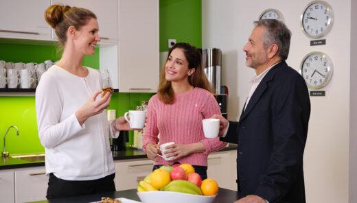 Fika på kontor med kollegor vid kaffemaskin