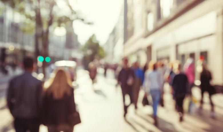 Människor på gågata i motljus