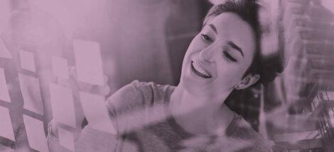 leende kvinna som sätter upp post its på glasvägg