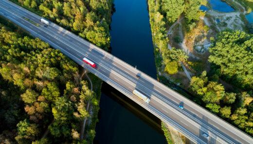 Vy över bro över vatten. Trafik, Grönskande träd.