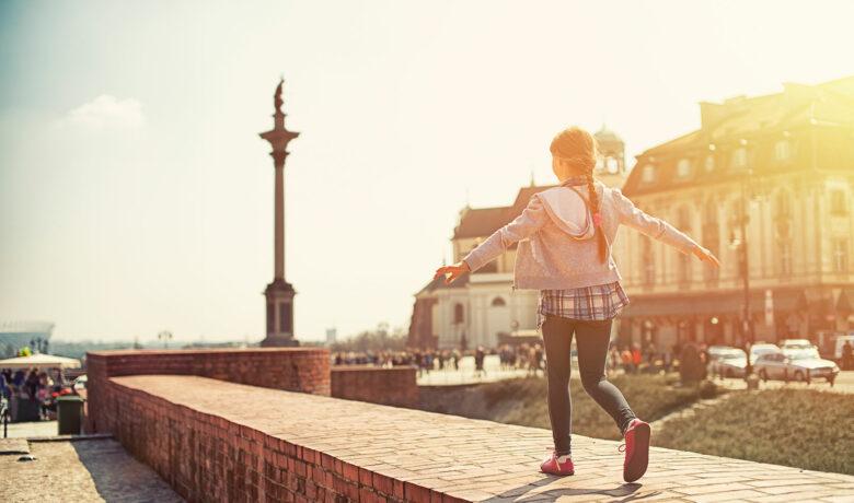 flicka balanserar på mur
