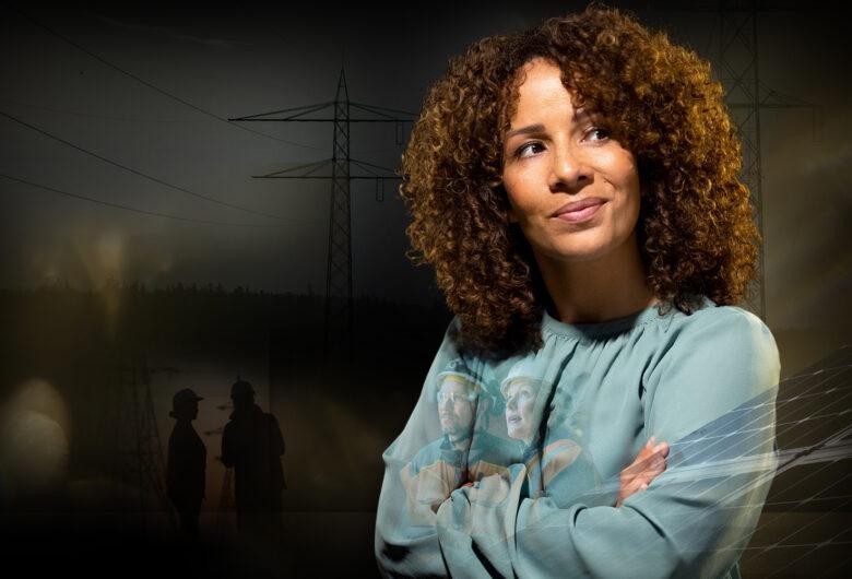 Kvinna med blå topp och mörk bakgrund, solceller i förgrunden